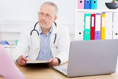 Male doctor at the table attentively listening to patient complaints.  royalty free stock photos