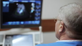 Male doctor taking a sonogram of abdomen and looking on the screen. Ultrasound device the hospital. Focus on the doctor`s glasses and blured screen on the stock footage