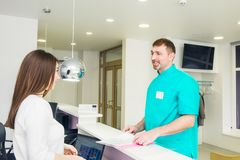 Male doctor talking and discuss working shedule with young friendly female receptionist at hospital reception desk. Occupation, st royalty free stock photography