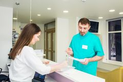Male doctor talking and discuss working shedule with young friendly female receptionist at hospital reception desk. Occupation, st. Aff interaction concept stock photography