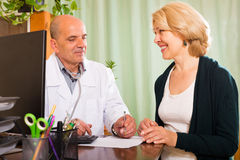 Male doctor talking with  mature female patient Stock Image