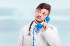 Male doctor talking on the phone. And holding money in his coat on blue background Stock Photo