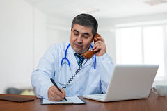 A male doctor talking on the phone. A male doctor is sitting at the table and talking on the phone. The doctor writes information to the notebook. Medical Royalty Free Stock Images
