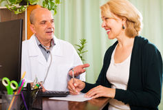 Male doctor talking with smiling mature patient Royalty Free Stock Photo