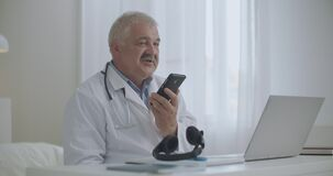 Male doctor is talking by speakerphone in mobile phone in his office in clinic, recording voice message, consulting