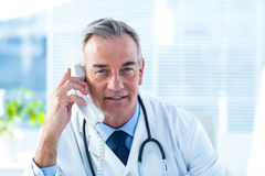Male doctor talking on telephone in clinic. Portrait of male doctor in conversation through telephone at clinic Stock Photography
