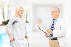 Male doctor talking to female patient with crutches in hospital. Corridor Royalty Free Stock Photo