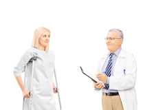 Male doctor talking to female patient on crutches. Isolated on white background Royalty Free Stock Image
