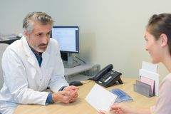 Male doctor talking to female patient stock photography