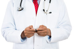 Male doctor texting on his phone Royalty Free Stock Photos