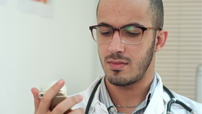 Male doctor texting on a smartphone. Close up shot. Professional shot on BMCC RAW with high dynamic range. You can use it e.g. in your commercial video stock footage