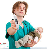 Male doctor with thermometer and baby boy. Male doctor in green uniform examining baby boy, white background Royalty Free Stock Photography