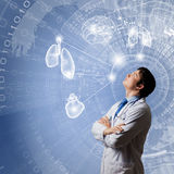 Male doctor thinking. Young concentrated male doctor with arms crossed against digital background Royalty Free Stock Photography