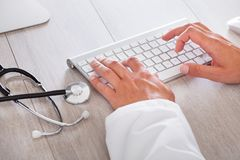 Male doctor typing on computer keyboard Stock Photography
