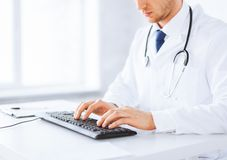Male doctor typing  on the keyboard. Close up of male doctor typing  on the keyboard Royalty Free Stock Photos