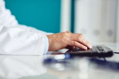 Male doctor typing on keyboard in the office. Close up Stock Photo