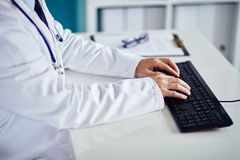 Male doctor typing on keyboard in the office. Male doctor typing on keyboard in medical clinic Stock Photos