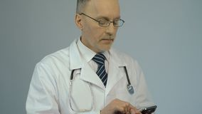 Male doctor typing message on modern smartphone, using smart gadget for work. Stock footage stock video
