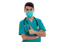 Male doctor in uniform and mask with stethoscope showing thumbs up isolated on white background Stock Photography