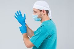 A male doctor in uniform pulls gloves on his hands. Isolation. royalty free stock image