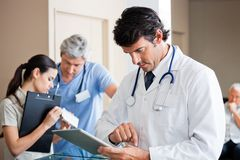 Male Doctor Using Digital Tablet. Mid adult male doctor using digital tablet with people in background Stock Photo