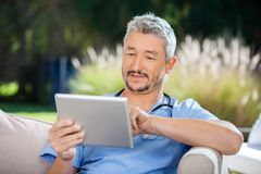 Male Doctor Using Digital Tablet While Sitting On Stock Images