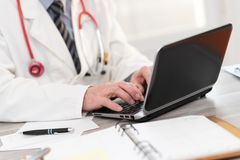 Male doctor using laptop royalty free stock photography