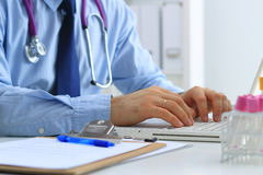 Male doctor using a laptop, sitting at his desk Stock Images