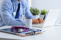 Male doctor using a laptop, sitting at his desk with medical stethoscope Royalty Free Stock Image