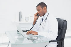 Male doctor using phone and laptop at medical office. Side view of a concentrated male doctor using phone and laptop at medical office Royalty Free Stock Image