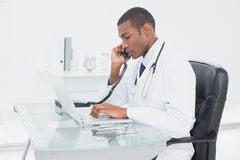 Male doctor using phone and laptop at medical office. Side view of a concentrated male doctor using phone and laptop at medical office Royalty Free Stock Photos