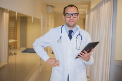 Male doctor using a tablet computer. In a hospital corridor. Male doctor using a tablet computer. In a hospital corridor Royalty Free Stock Photo