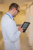 Male doctor using a tablet computer. In a hospital corridor. Stock Photos
