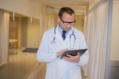Male doctor using a tablet computer. In a hospital corridor. Royalty Free Stock Image