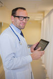 Male doctor using a tablet computer. In a hospital corridor. Male doctor using a tablet computer. In a hospital corridor Royalty Free Stock Images