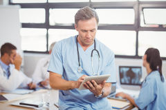 Male doctor using tablet in conference room. And colleagues discussing in background Royalty Free Stock Images