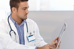 Male doctor using tablet pc. Young male doctor using tablet computer, side view Stock Image