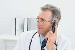 Male doctor using telephone at office Stock Photo