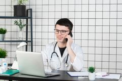 Male doctor using telephone while working on computer at table in clinic stock image