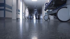 Male doctor walking through the long hallway. In hospital stock footage