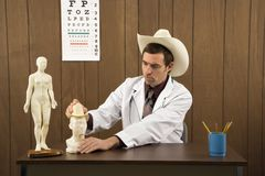 Male doctor wearing cowboy hat playing with figurine. Stock Photos