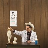 Male doctor wearing cowboy hat playing with figurine. Royalty Free Stock Photography