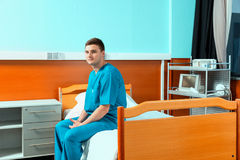 Male doctor wearing uniform sitting on a bed and waiting for his Stock Photography