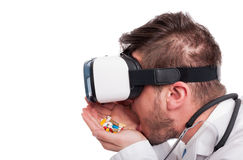 Male doctor wearing vr glasses and eating pills. Male doctor wearing vr glasses and eating many pills on white background as drug addiction concept Stock Photos