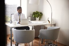 Male Doctor Wearing White Coat In Office Sitting At Desk Working On Laptop stock photo