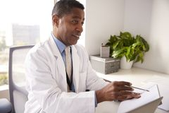 Male Doctor Wearing White Coat In Office Sitting At Desk Working On Laptop stock photography