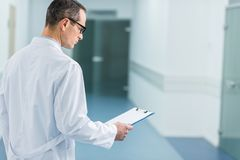 Male doctor in white coat reading diagnosis. In hospital royalty free stock photo