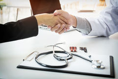 Male doctor in white coat shaking hand to female colleague Stock Image
