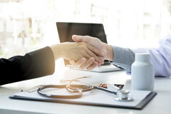 Male doctor in white coat shaking hand to female patient after s royalty free stock image