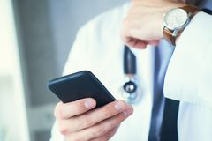 Male doctor in white coat is using a modern smartphone device with touch screen. Doctor hands with mobile phone. Doctor hands with mobile phone. Male doctor in stock photography